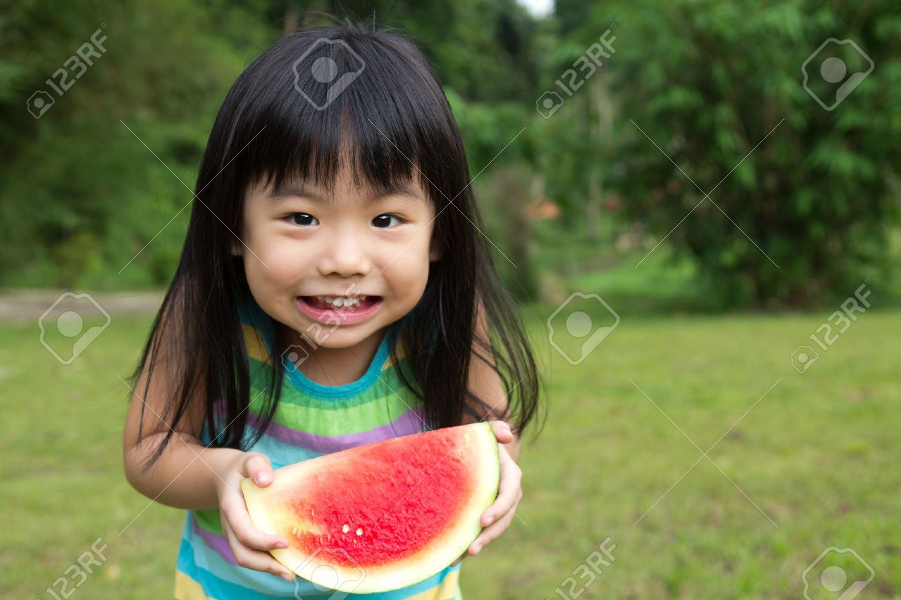 Little Asian kid with a piece of watermelon in park Stock Photo - 12941863