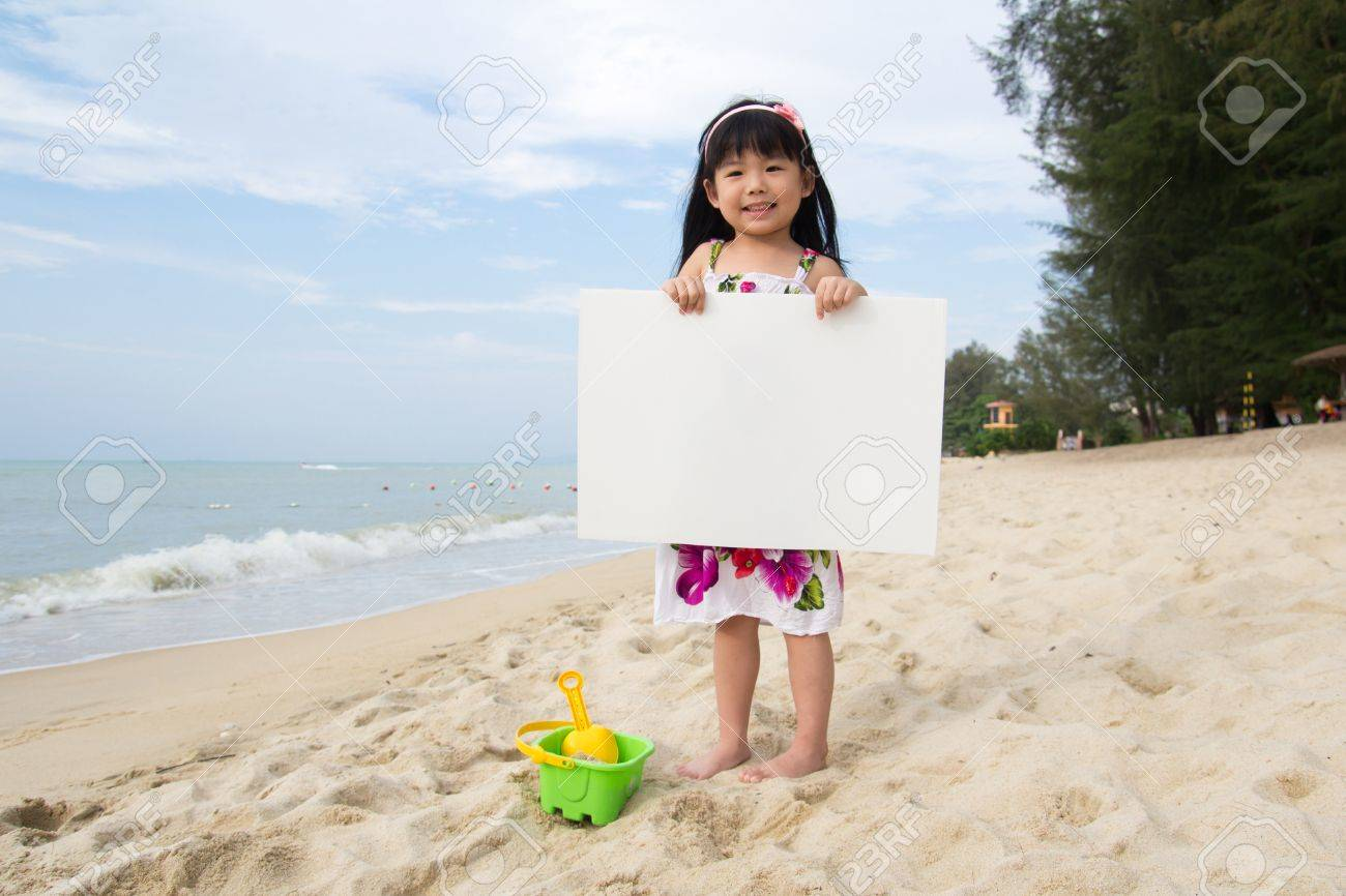 Little child girl holds a white board at beach Stock Photo - 13047990