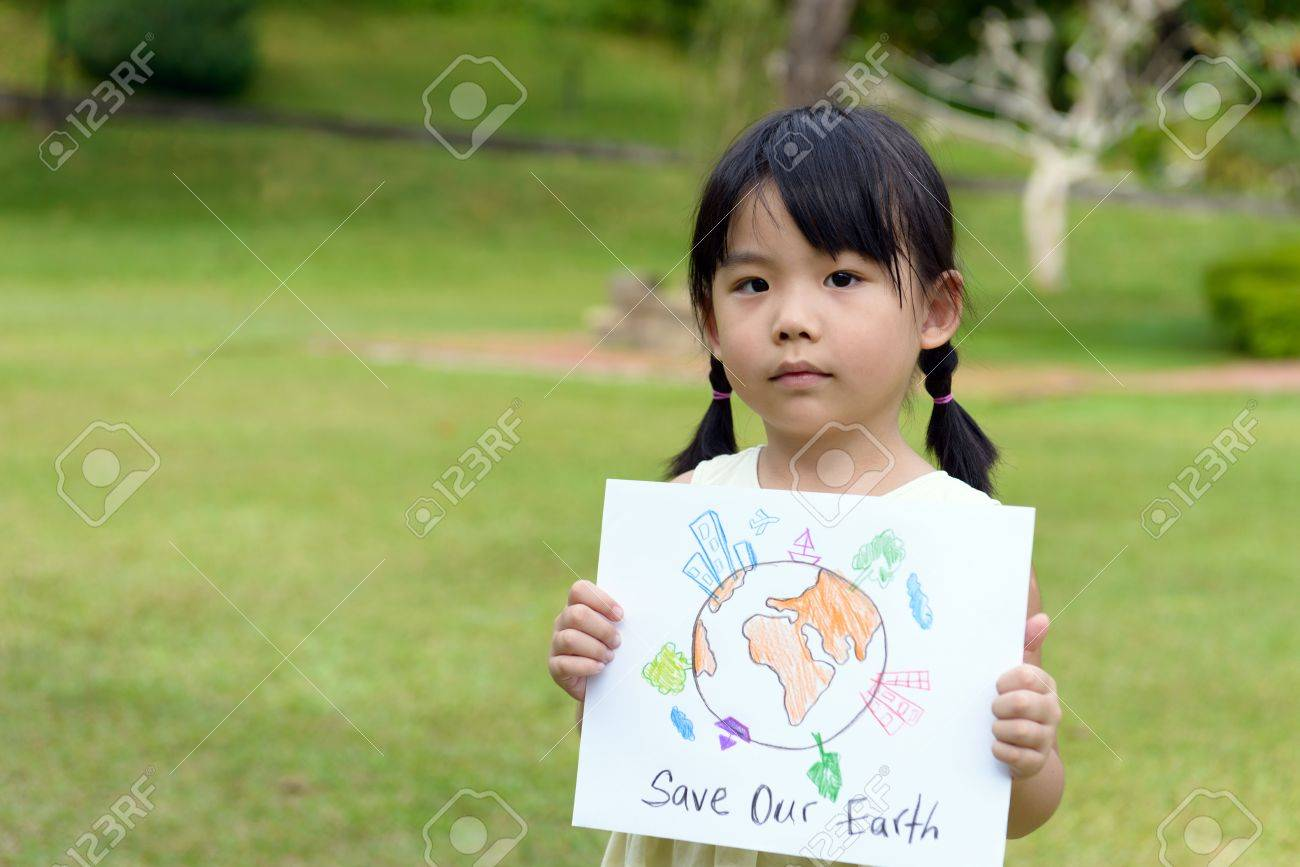 little kid showing save our earth drawing in a park stock photo