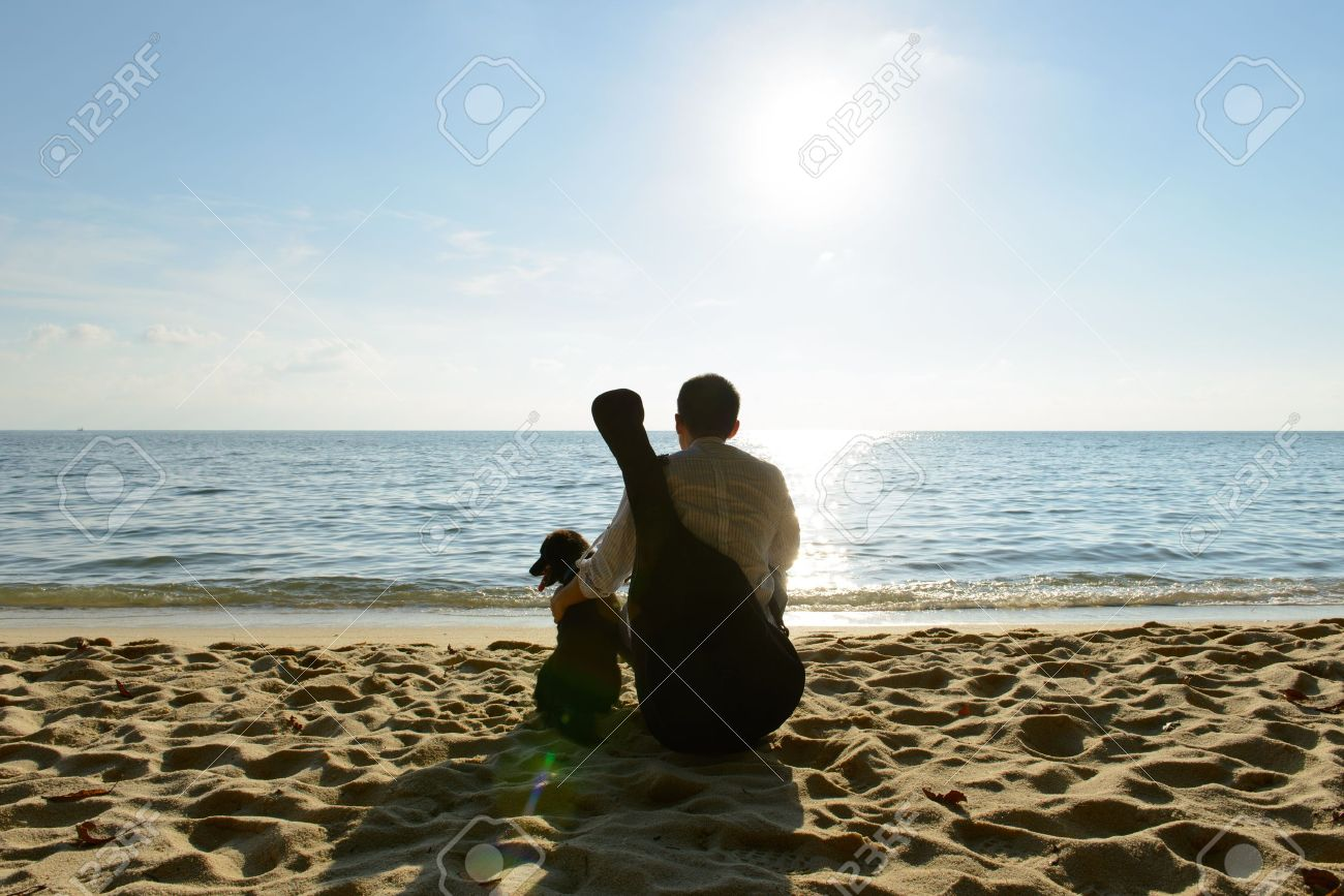 Lonely man with his dog and guitar at beach - 18810392