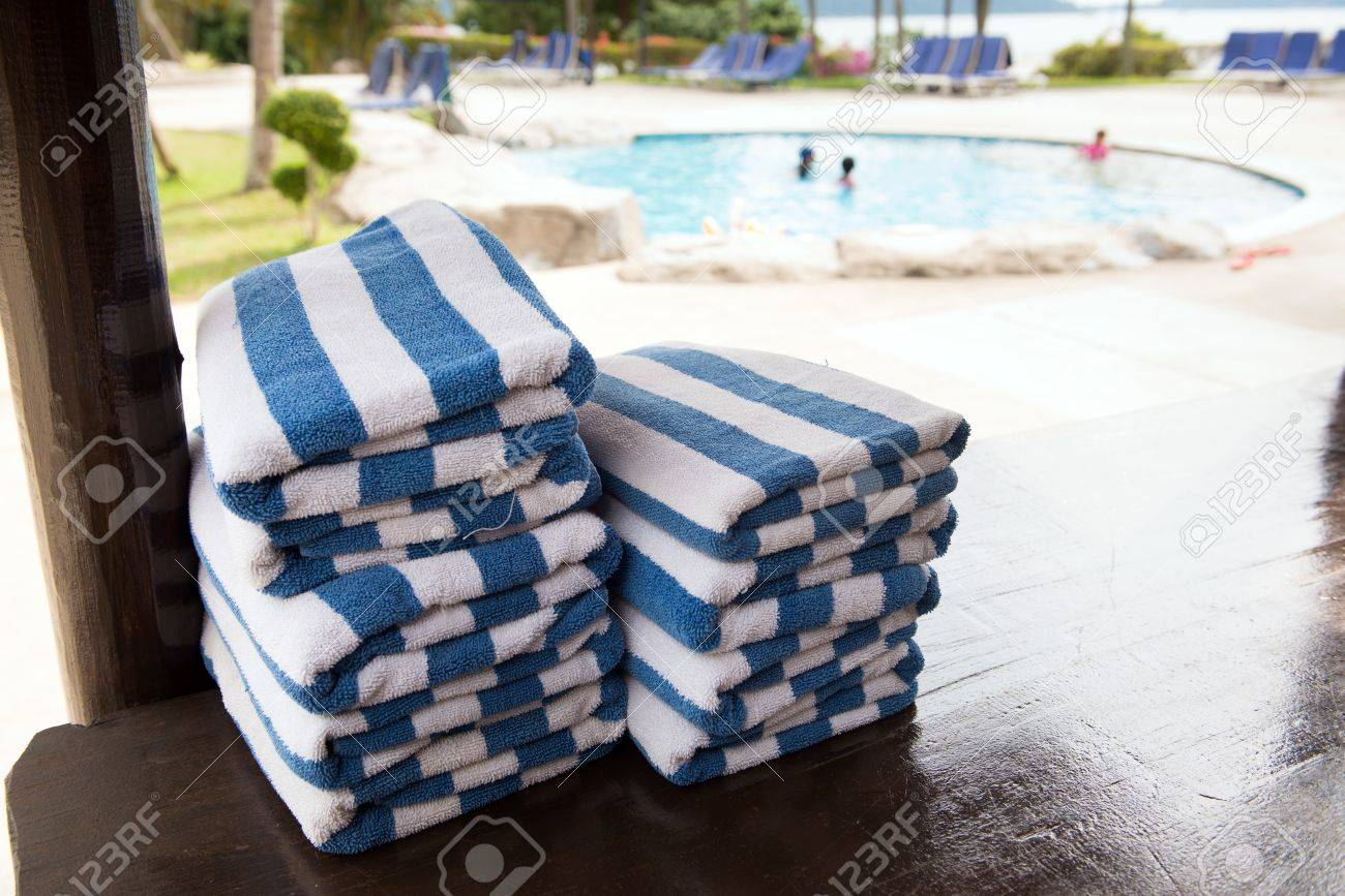 Blue Stripe Towels Stacked At The Side Of Swimming Pool Stock Photo ...