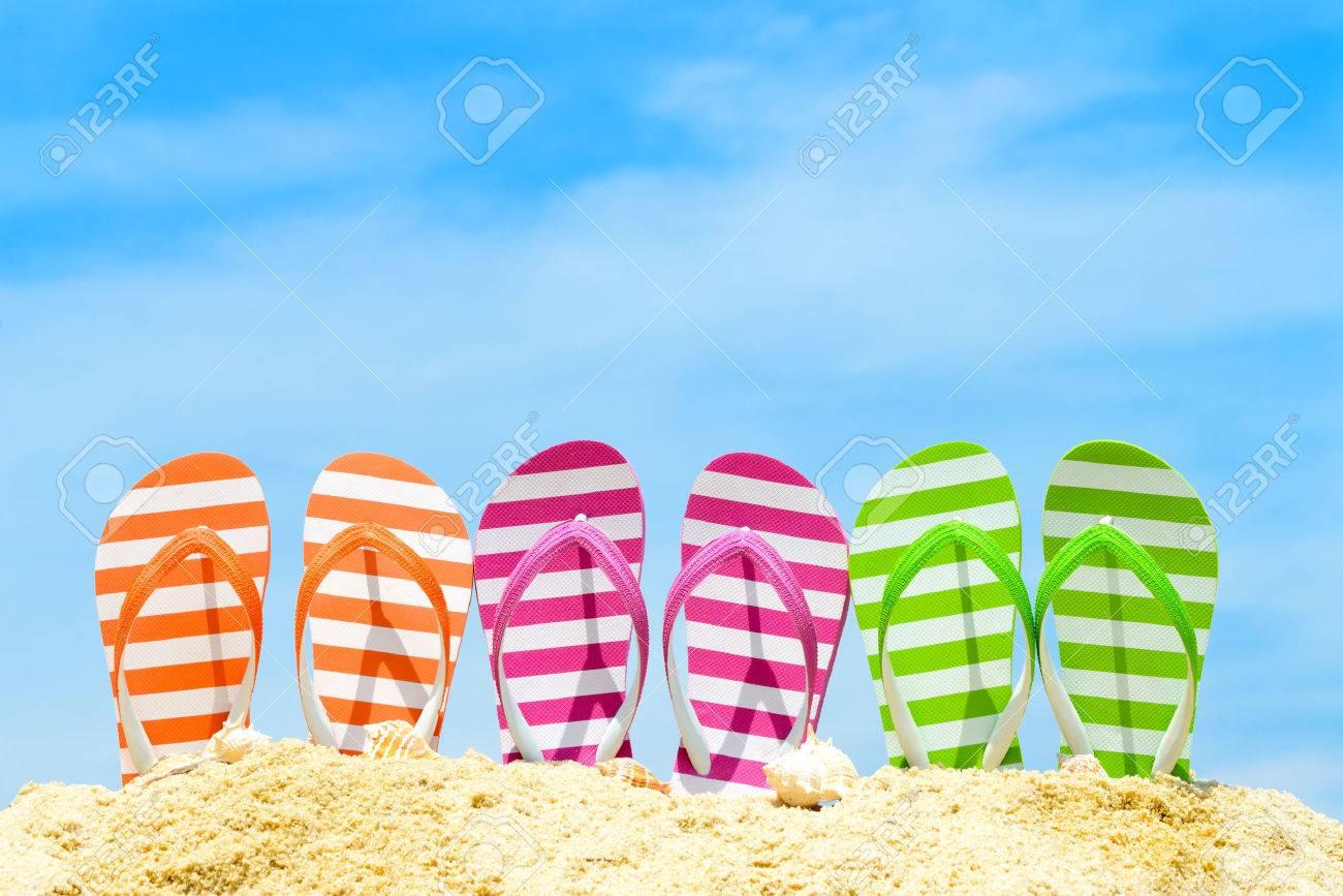 Row of multicolor flip flops on beach against blue sky - 39643499
