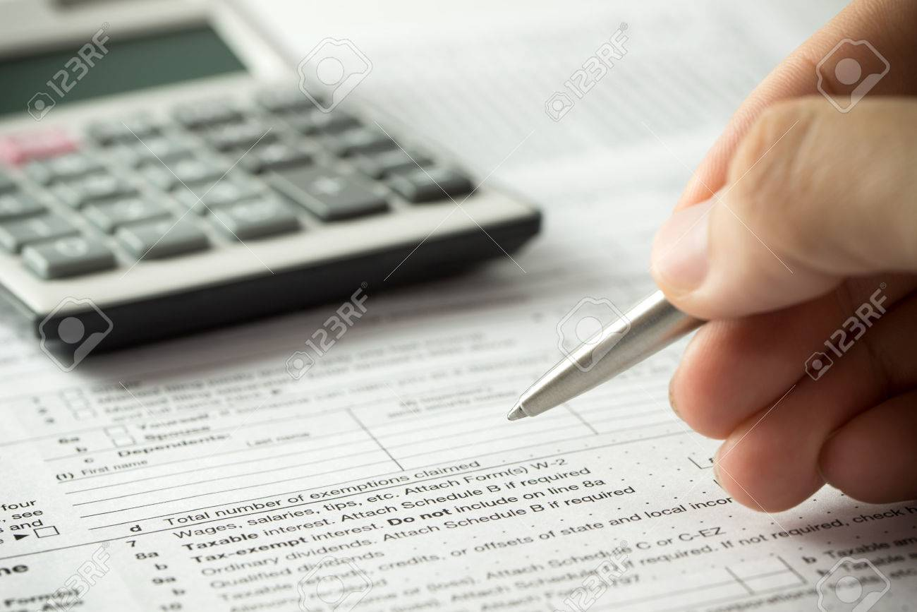 US individual income tax return form with pen and calculator - 55619036