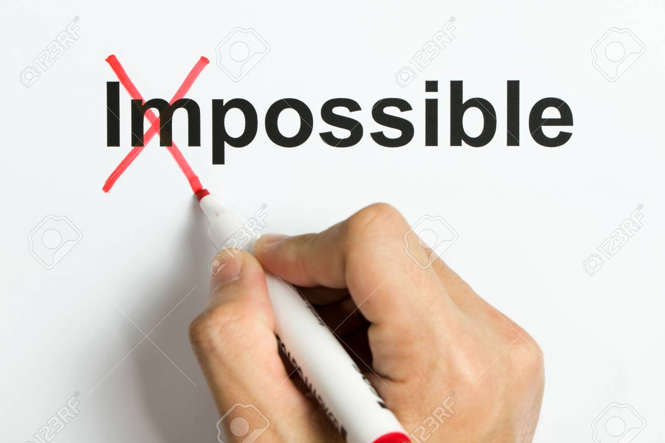 Hand holding marker pen to cross out the word impossible to reveal