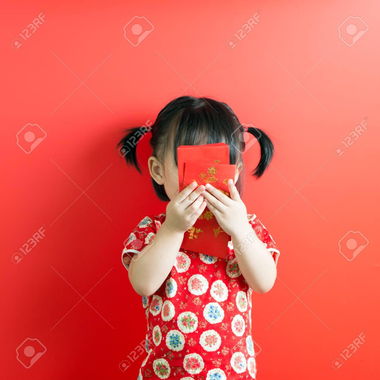 Little Asian girl holding red envelope on red background - 93215259
