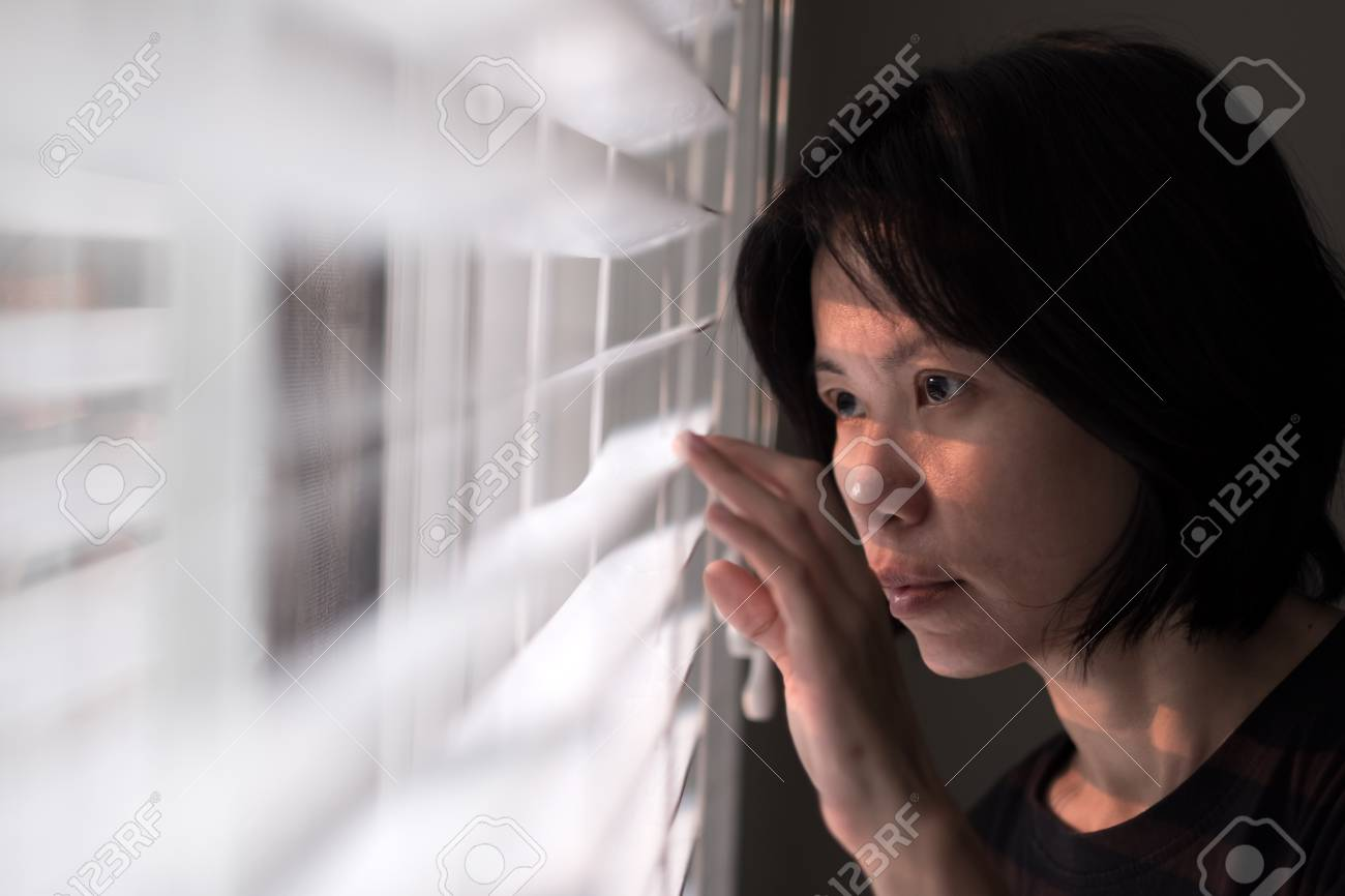 Portrait of young Asian lady peeking out of window - 108071604