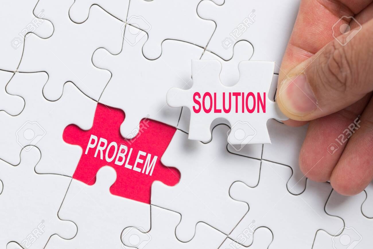Hand holding piece of white jigsaw puzzle with word problem and solution. - 122570408