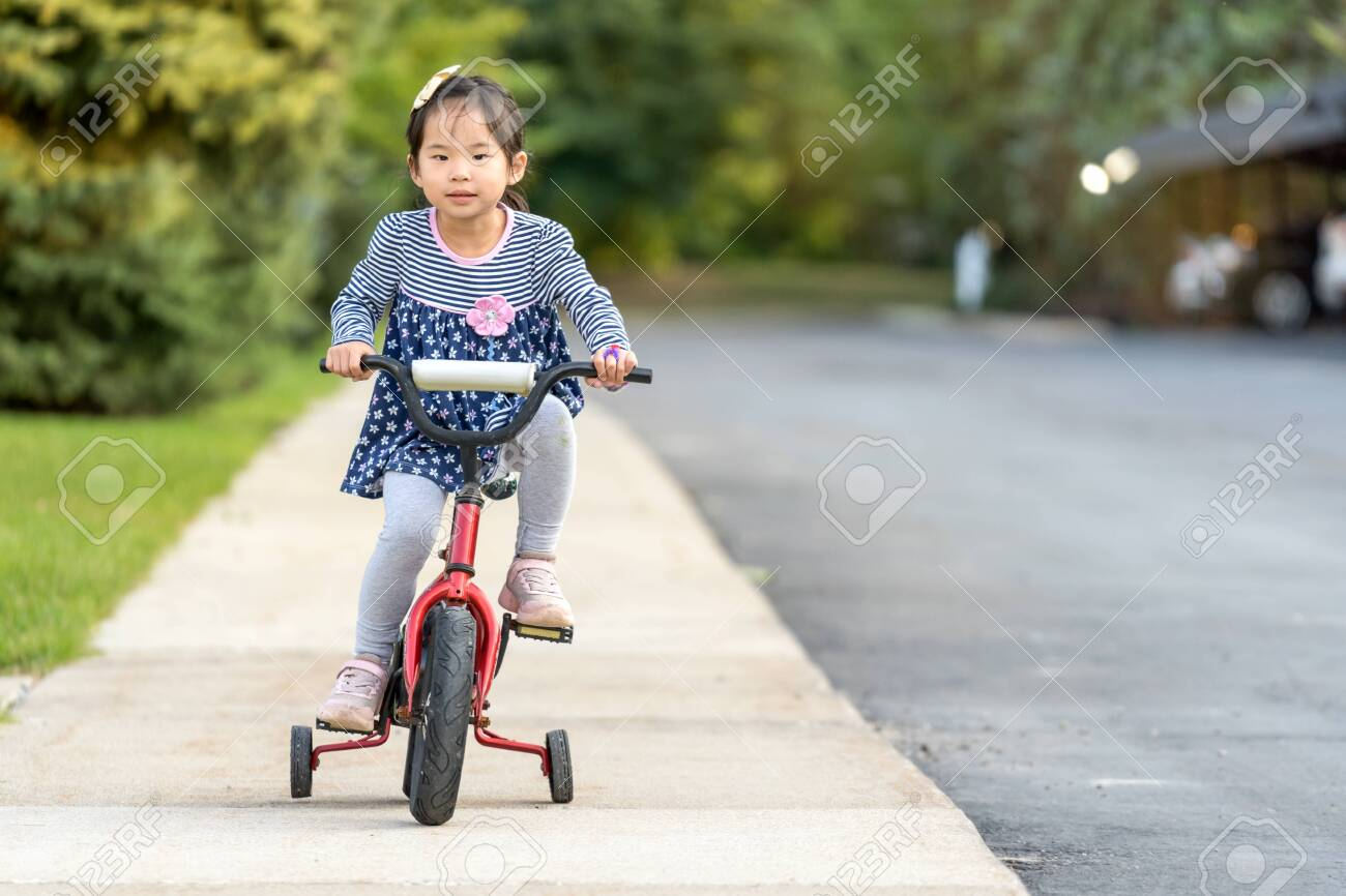 Cute little Asian girl learning ride a bicycle without wearing a helmet - 132068492