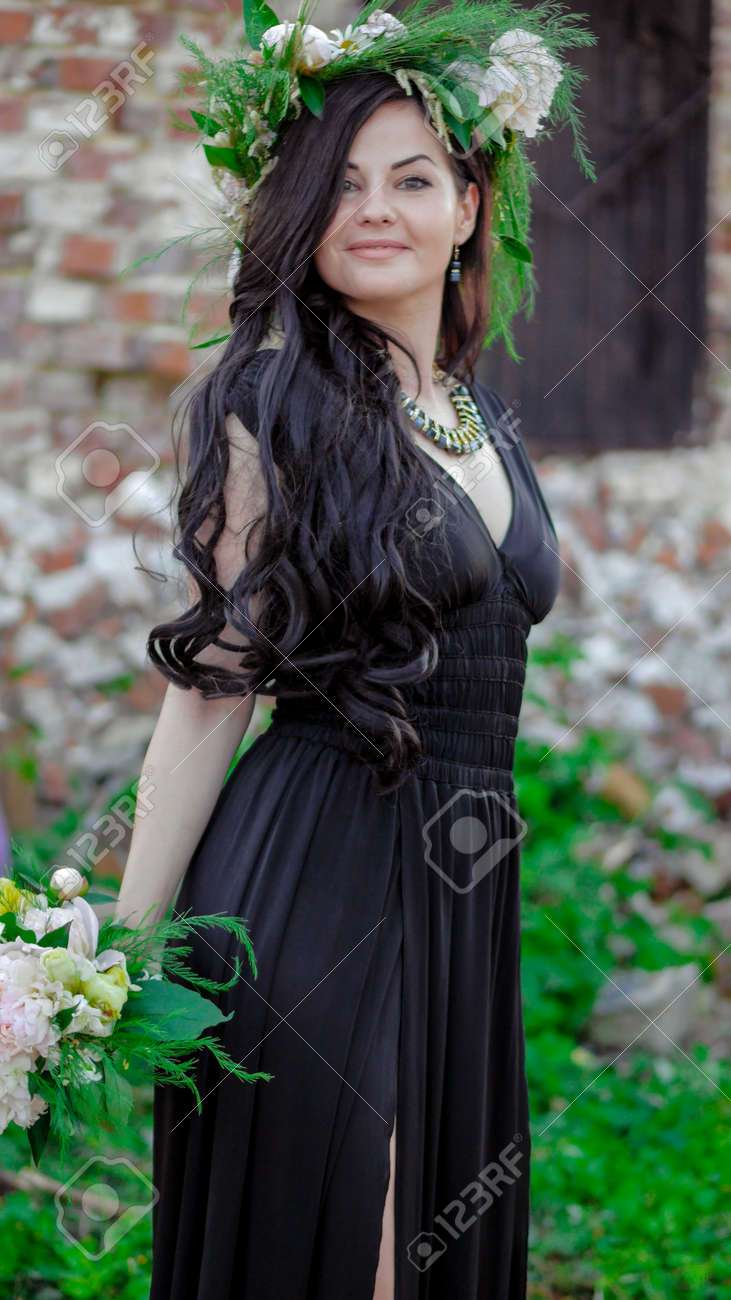 Woman in the spring. A wreath of meadow grass and flowers is worn on the brunettes head. White peonies adorn the head of a young lady. A girl in a long black sleeveless dress. - 151458813