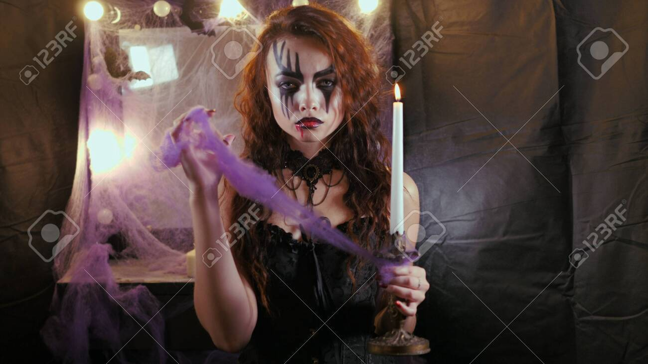 Easy Halloween Makeup. The girl with the picture on her face. Photo portrait. Woman holds a paraffin candle. - 146761287