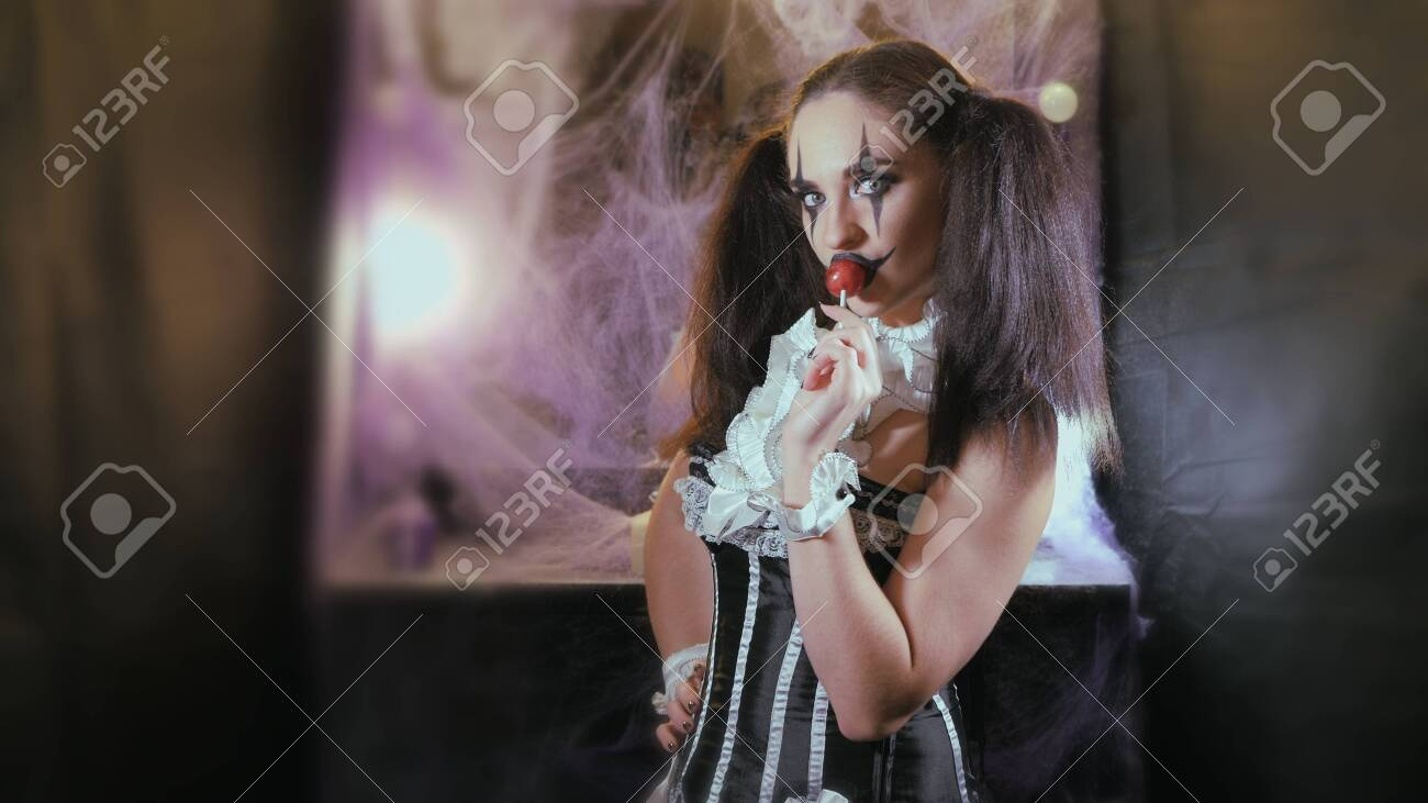 Portrait of a woman. A clown with a smile in corset with a white collar on the neck. Model with makeup for Halloween. Woman flirting. The girl with the red Lollipop. The woman takes a candy in her mouth and licks it. - 146771892