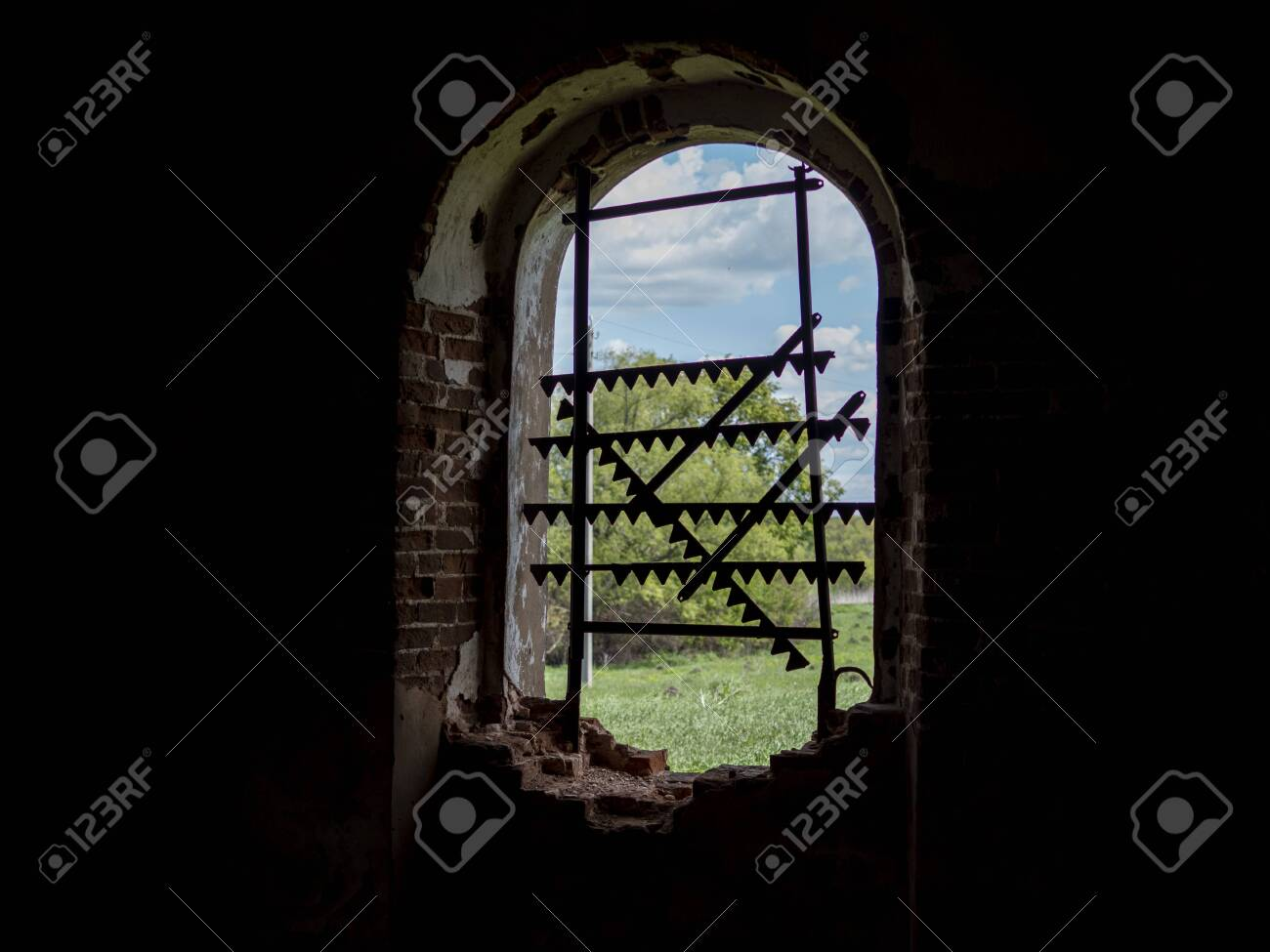 Windows of an ancient temple, in the wall of red brick, in the form of an arch. The hole in the wall is sealed with metal bars with teeth. - 149481540