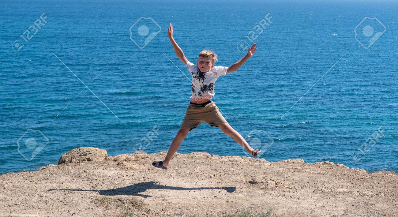 A fair-haired boy against the blue sea. - 155752464