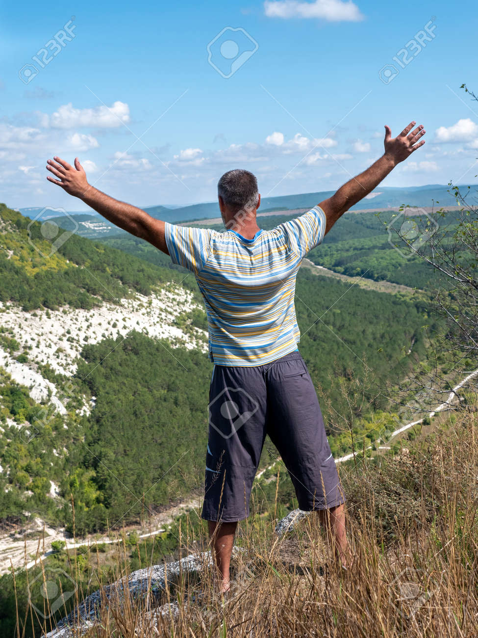 An adult man with his arms spread wide, seen from the back, stands on the edge of a precipice. - 155752173