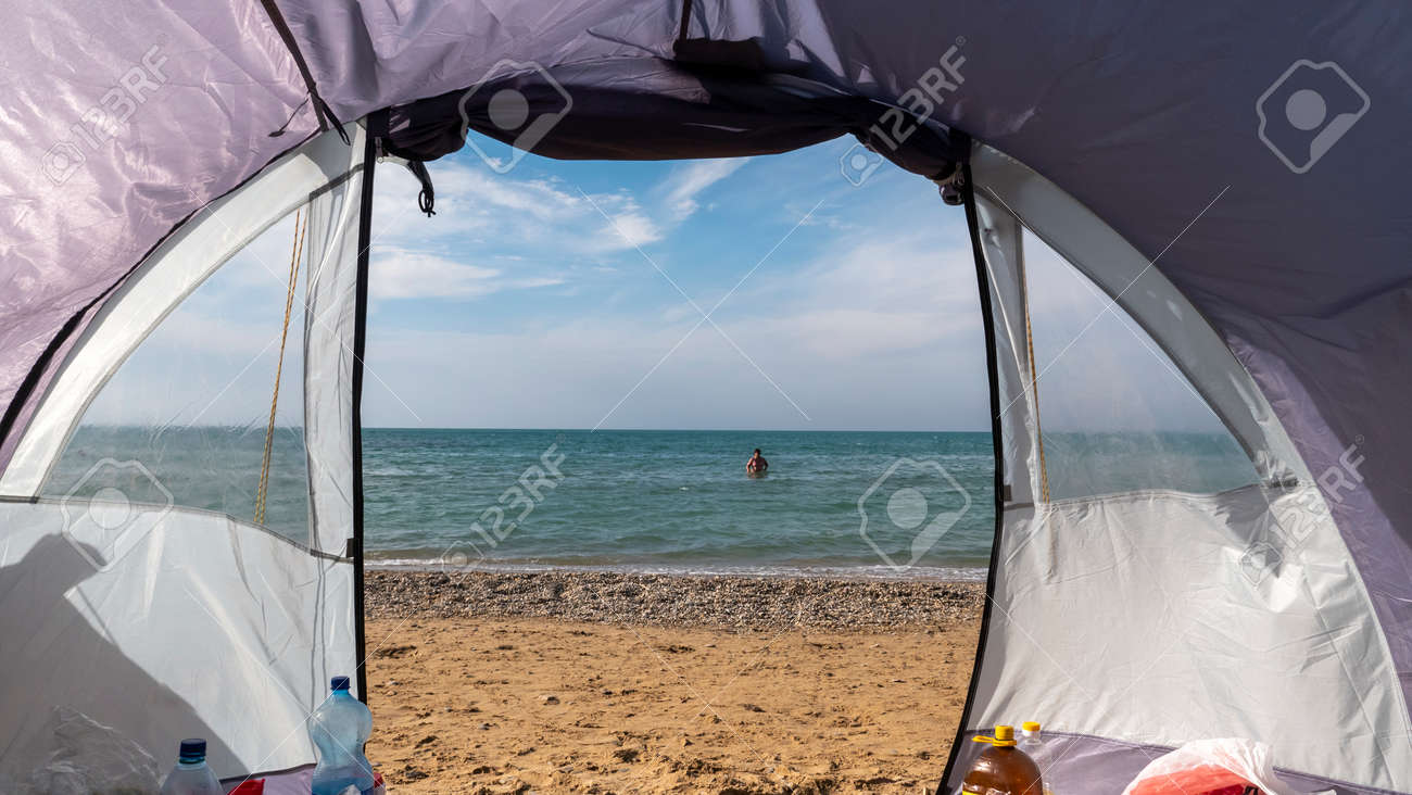 View through the open entrance to the tent on the sea. Sandy beach. - 156717725