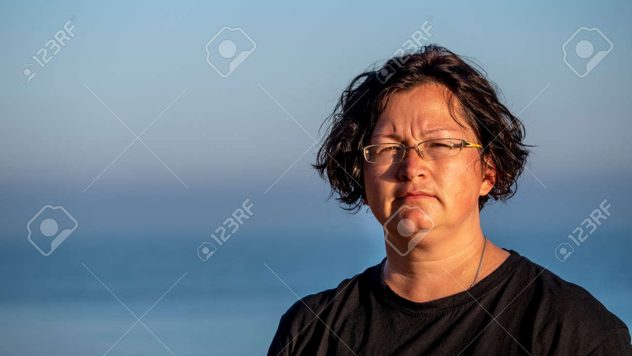Portrait of a woman against the sea. - 157302974