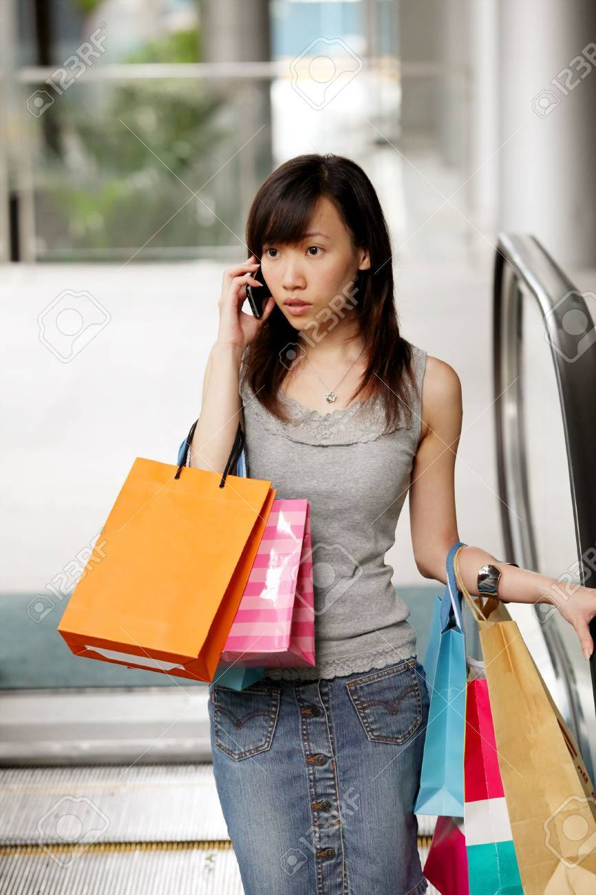 Happy Shopper Smiling with Shopping Bags on Phone Stock Photo - 5735803