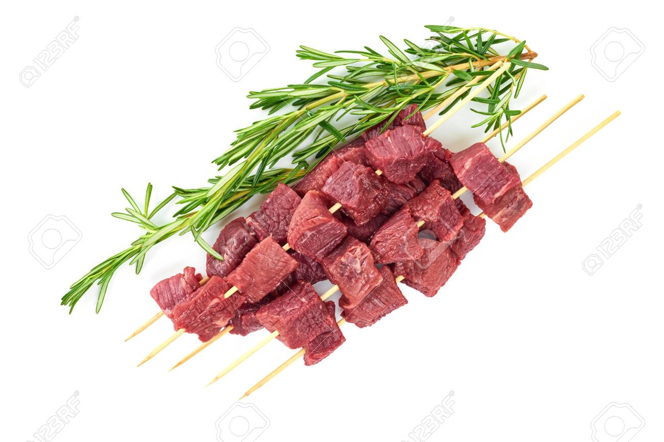 Pieces of fresh meat on bamboo skewers and a branch of rosemary on a white background. Fresh meat skewers on skewers and a branch of rosemary. The view from the top. - 146098291