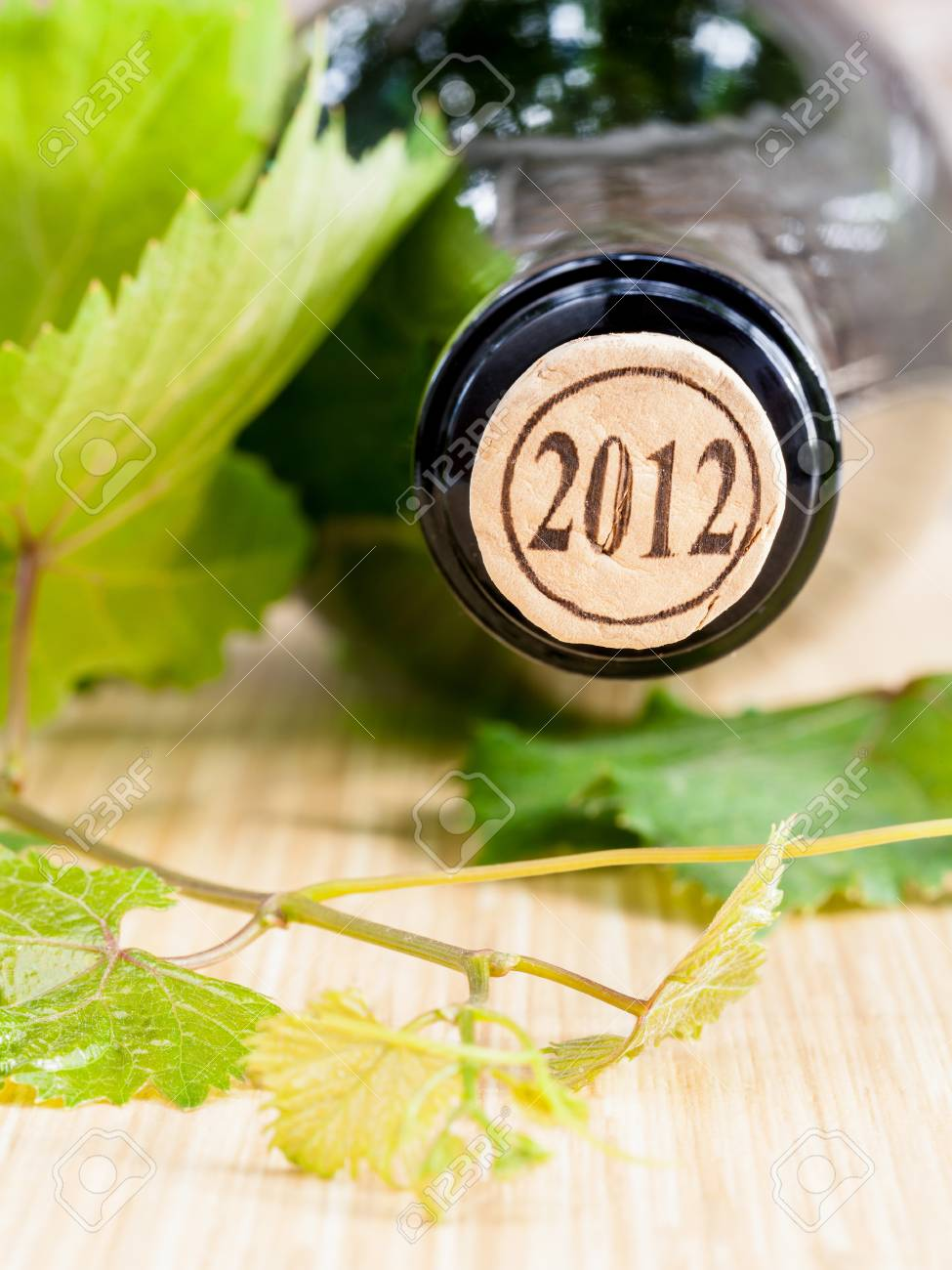 Wine Bottle With Vine And Wine Cork Put On The Board Stock Photo