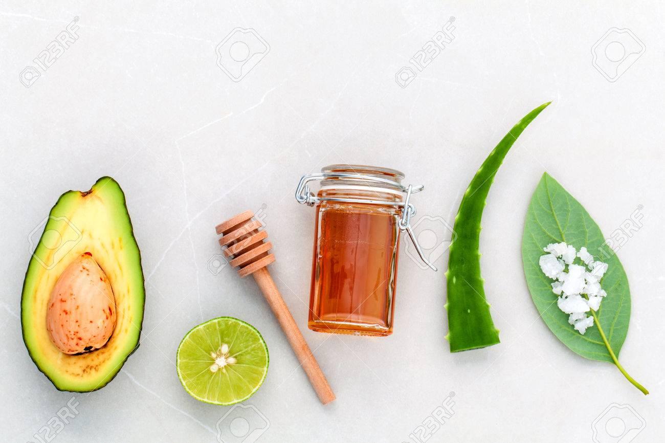 Alternative skin care and scrub fresh avocado , leaves ,sea salt , oils, lime and honey on marble background. - 48792733