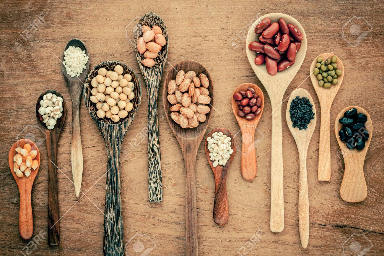 Assortment of beans and lentils in wooden spoon on teak wood background. mung bean, groundnut, soybean, red kidney bean , black bean ,sesame, corn ,red bean and brown pinto beans . - 48792752