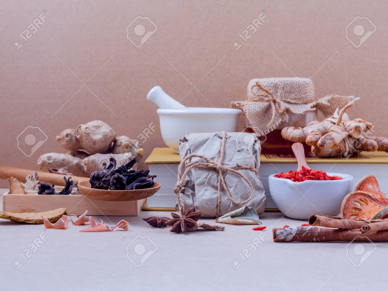 Alternative healthcare dried various Chinese herbs in wooden box and dried roselle in wooden spoon on medical textbook with mortar on brown background. - 51659570