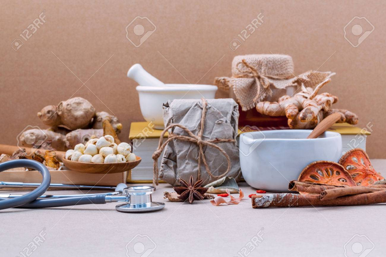 Alternative health care lotus seed in wooden spoon put on dried various Chinese herbs in wooden box and medical textbook with mortar on brown background. Depth of field selective focus on stethoscope. - 51662914