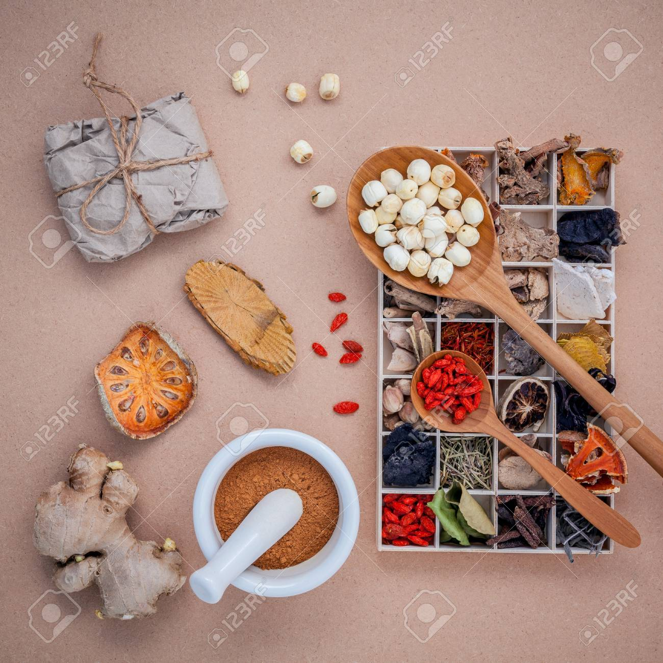 Alternative health care dried various Chinese herbs in wooden box , dried quince ,ginger and lotus seed in wooden spoon with mortar on brown background. - 51662999