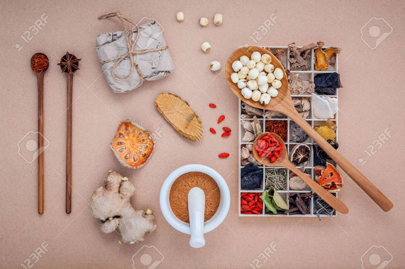 Alternative health care dried various Chinese herbs in wooden box , dried quince ,ginger and lotus seed in wooden spoon with mortar on brown background. - 51663137