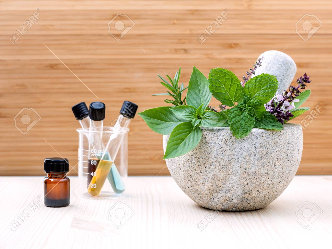 Alternative health care fresh herbs basil ,sage ,rosemary, mint and essential oil with mortar on wooden background. - 52945272