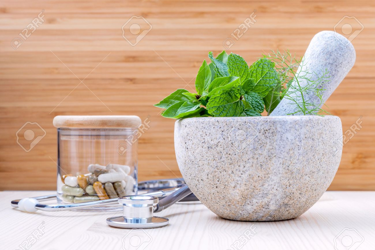 Fresh herbal leaves basil ,sage , mint ,holy basil ,fennel and capsule of herbal medicine alternative health care with stethoscope setup on wooden background. - 52945410