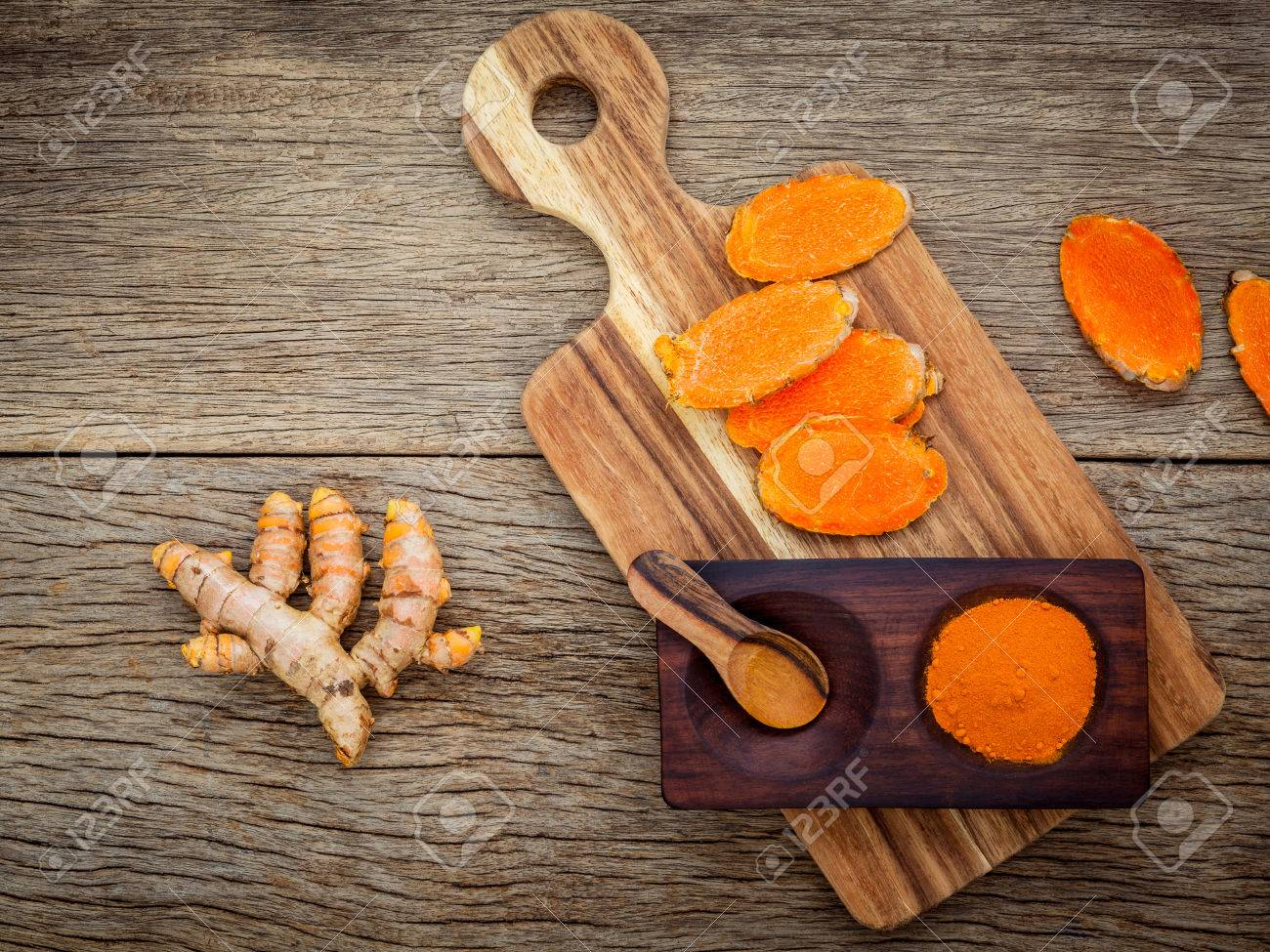 Homemade scrub curcumin powder and curcumin roots with cutting board set up on old wooden background. - 61128619