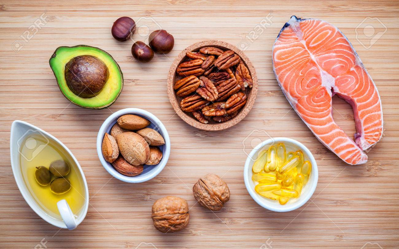 Selection food sources of omega 3 and unsaturated fats. Super food high vitamin e and dietary fiber for healthy food. Almond ,pecan ,hazelnuts,walnuts ,olive oil ,fish oil ,salmon on cutting board. - 66555018