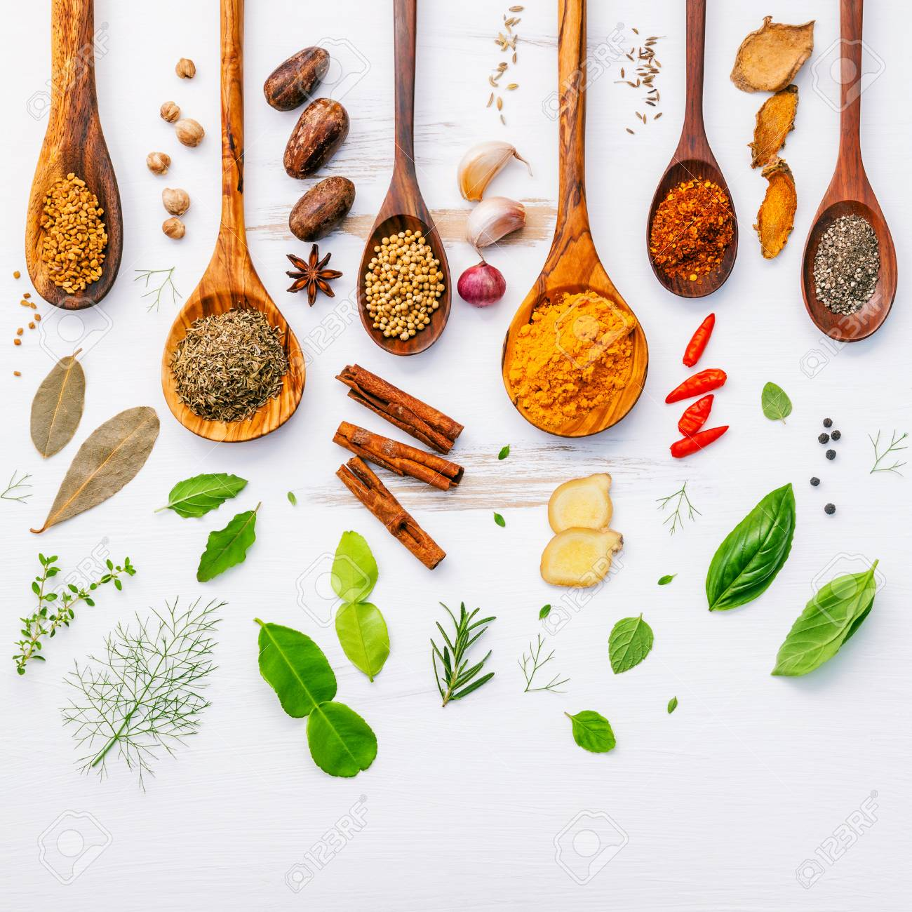 Various herbs and spices in wooden spoons. Flat lay of spices ingredients chilli ,pepper, garlic,dries thyme, cinnamon,star anise, nutmeg,rosemary, sweet basil and kaffir lime on wooden background. - 70652167