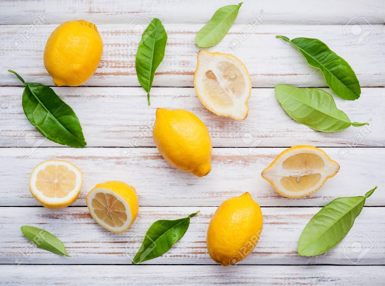 fresh lemons and lemons leaves on rustic wooden background