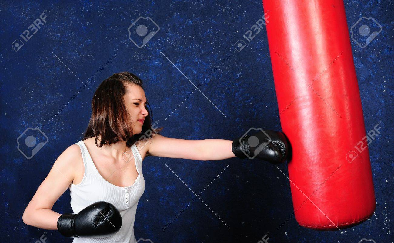 Young girl boxing a punchbag with all her efforts Stock Photo - 13248885