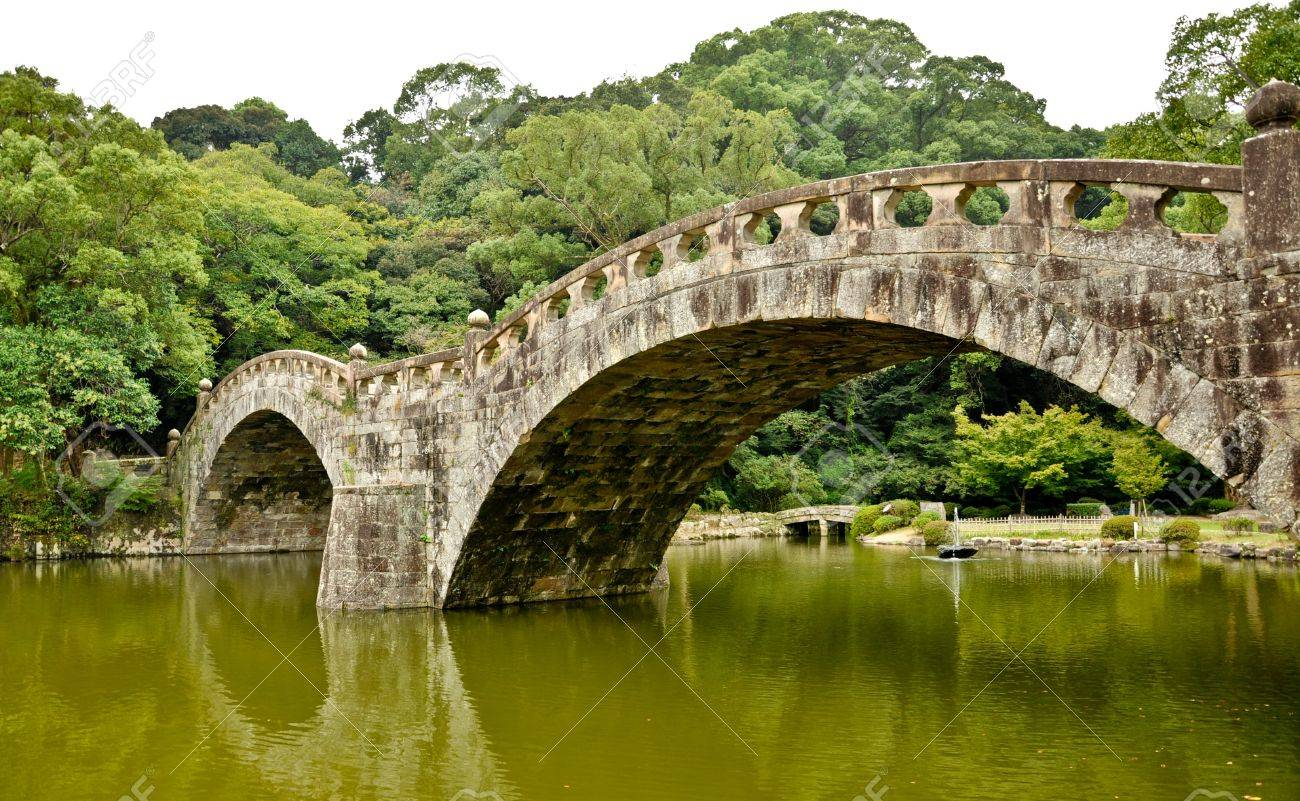 Japanese Garden Stone Bridge stone bridge in japanese garden at isahaya, japan stock photo