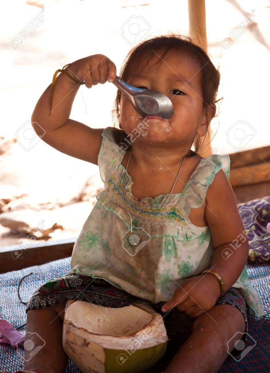 Little girl eat coconut in Laos Stock Photo - 14339781