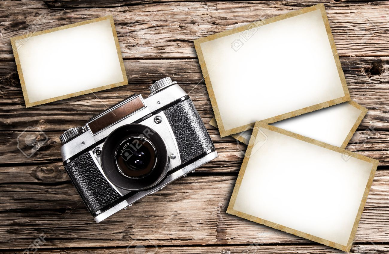 Old Vintage Camera On A Wooden Background With Blank Photo Frames ...