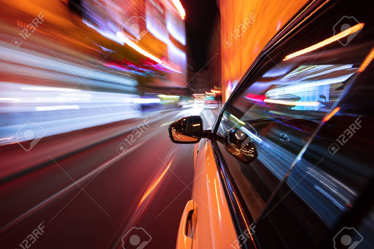 Speeding car driving in a night city. - 121887236