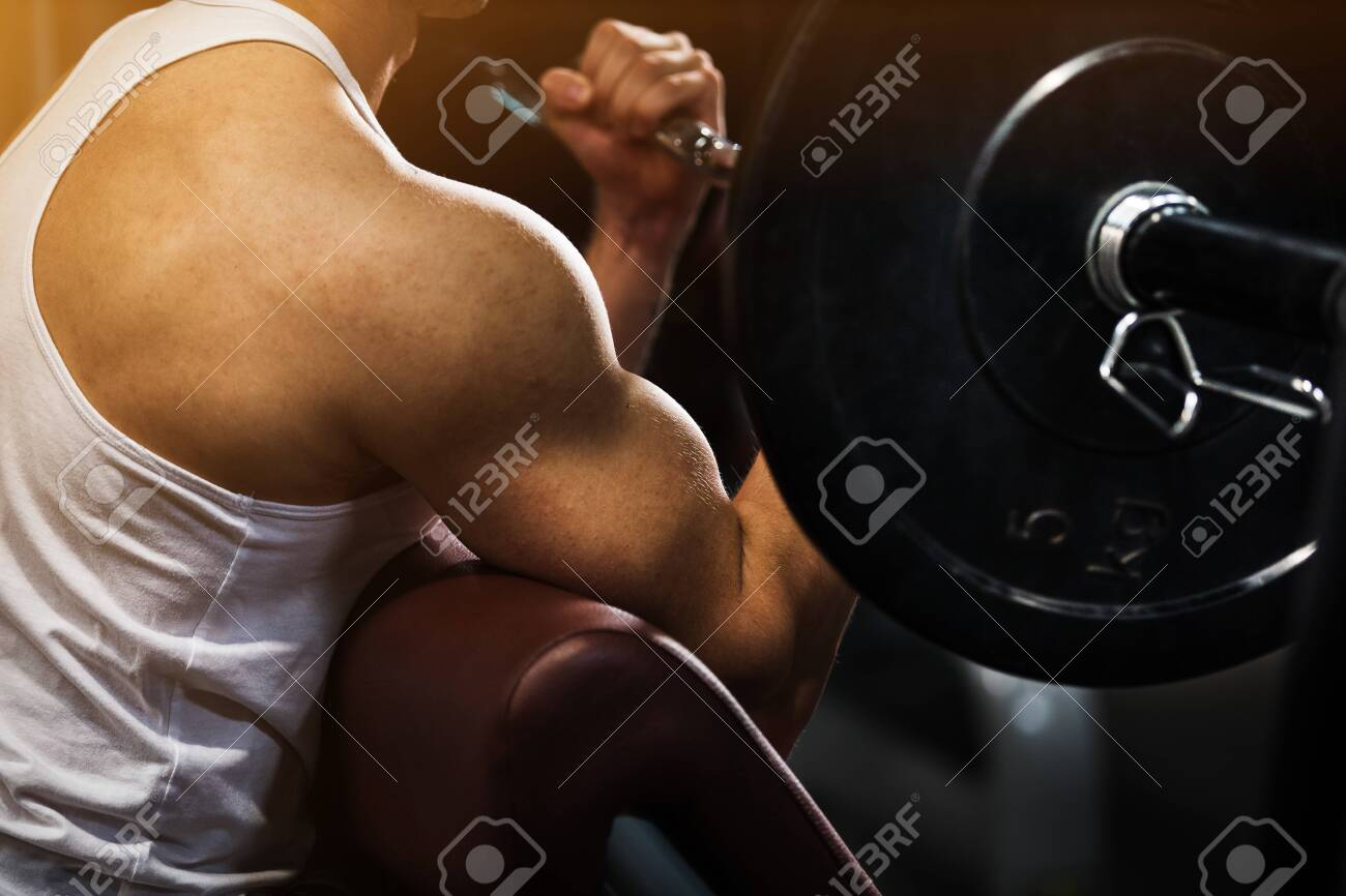 Muscular young man doing weight exercise for biceps with dumbbells - 129408912
