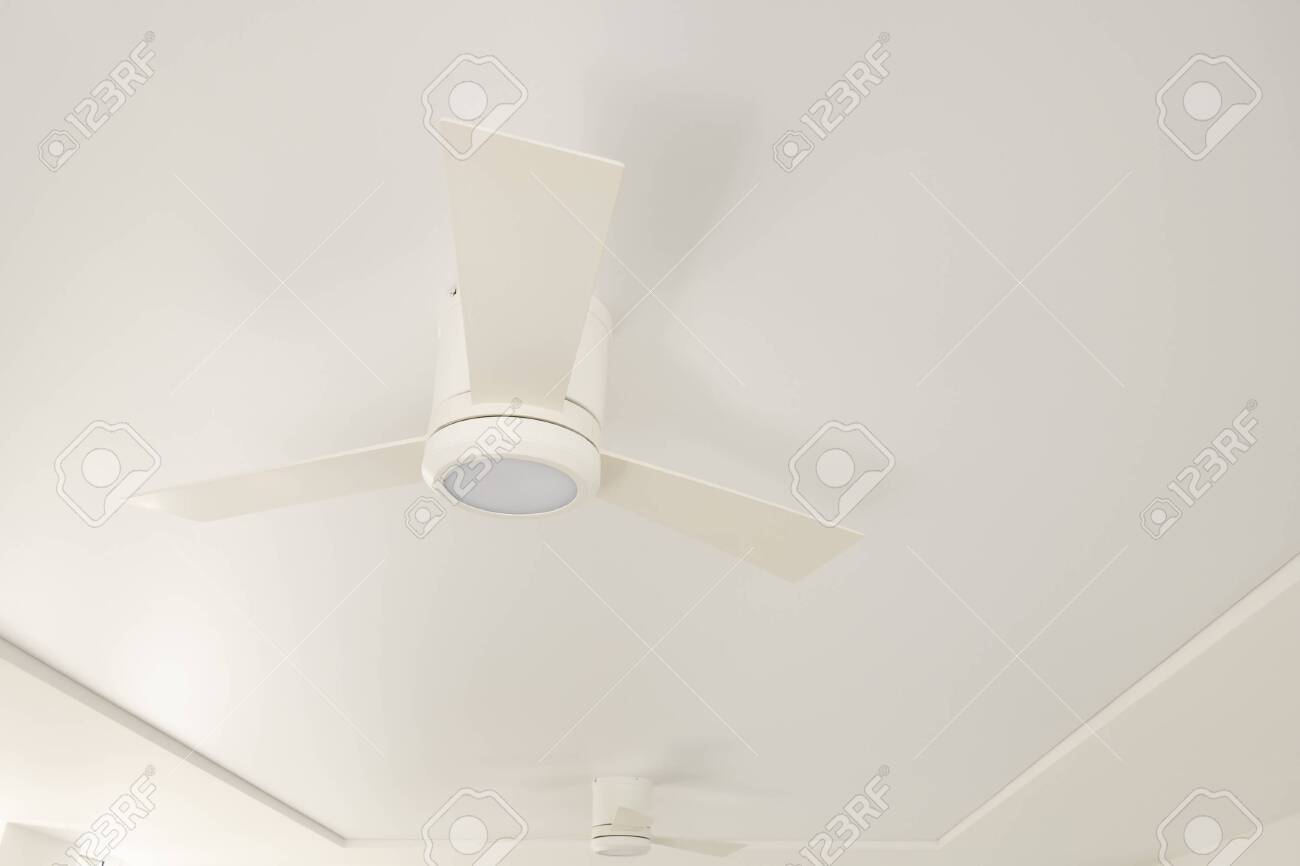 An overhead LED luminaire combined with a white ceiling fan on a white ceiling - 145315497