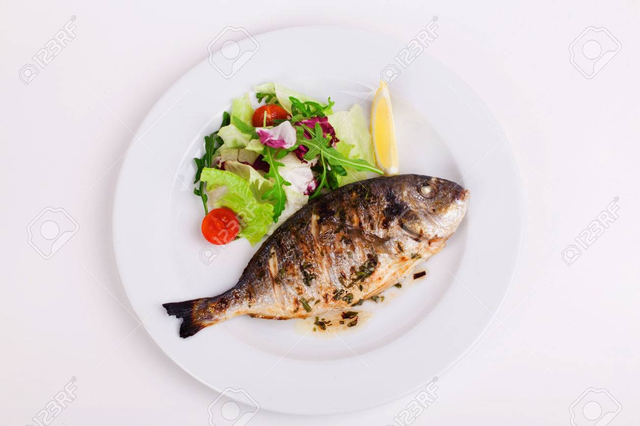 baked whole fish grilled on a plate with vegetables and lemon on top for the menu - 36761241