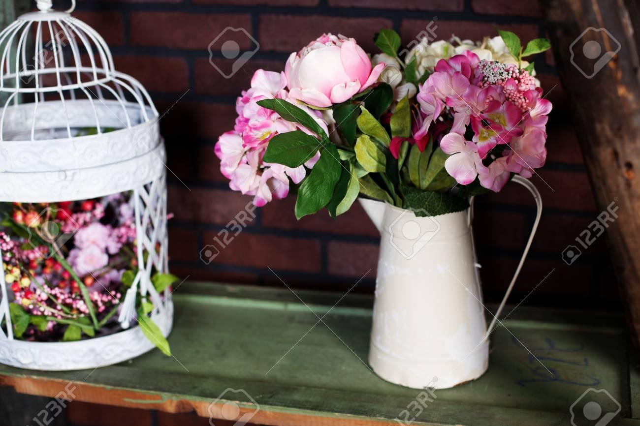 Delightful iron pitcher in the style of provence with silk flowers delightful iron pitcher in the style of provence with silk flowers peonies birdcage stock photo mightylinksfo