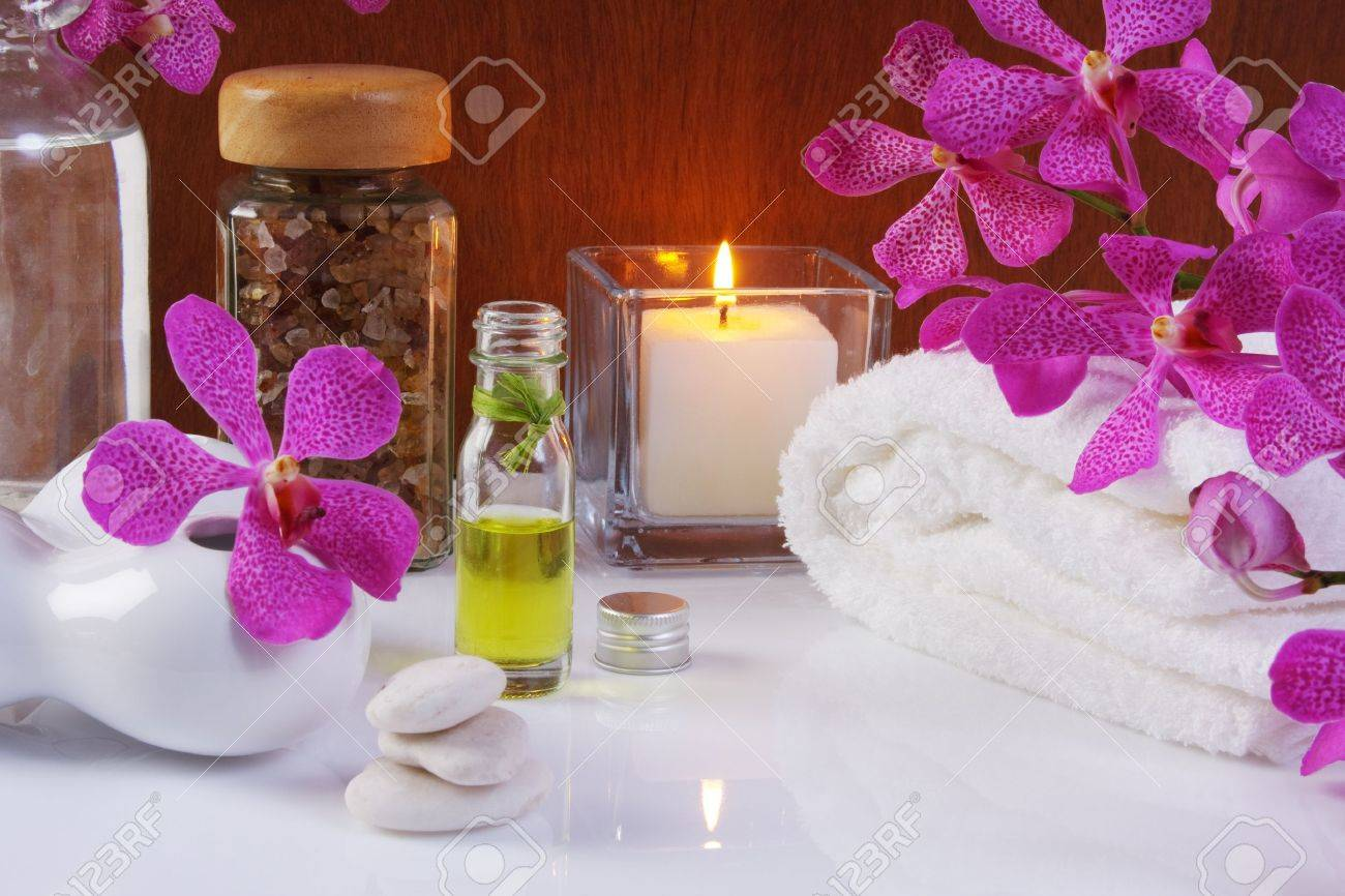 health spa with purple orchid, essentail oil, salt, towel, white stone and burning candle Standard-Bild - 13835517