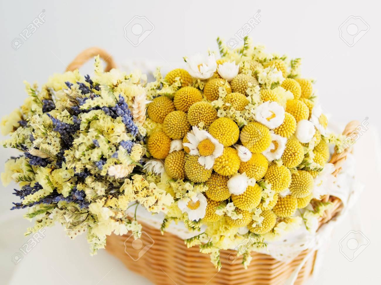 dos pequeos ramos de flores secas ponen en una canasta foto de archivo