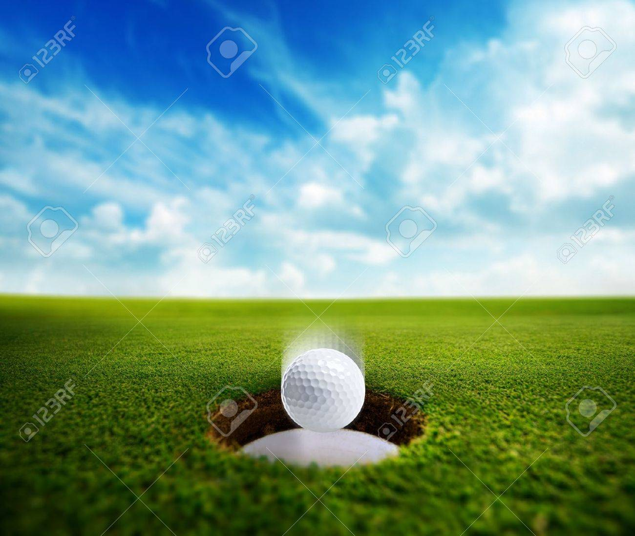 Golf ball falling into the cup on the green. Stock Photo - 20353991