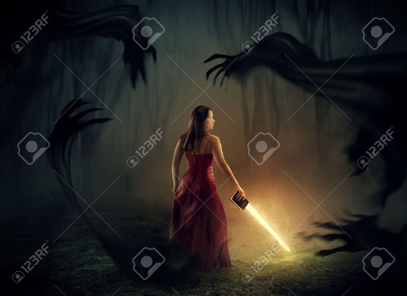 A woman holds a sword out of a Bible with dark demons around. - 36874144