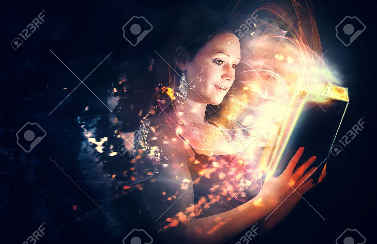 A woman reads a Bible with brilliant glowing lights. - 57162407