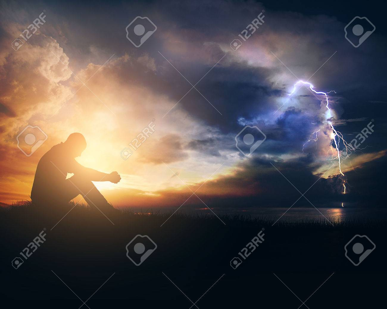 A man is praying through the sunrise and the storm - 57203770
